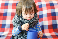 Lovely 2 years ill toddler in warm woolen scarf and cup of tea Royalty Free Stock Images