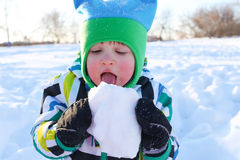 Lovely 2 years toddler boy eating snow Royalty Free Stock Image