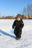 Lovely 2 years toddler walking with shovel in winter Royalty Free Stock Photos