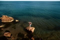 Lovely young adult couple on the rocks in the sea near the beach with big cliffs, Black Sea, Odessa, Ukraine, place for text set stock photos
