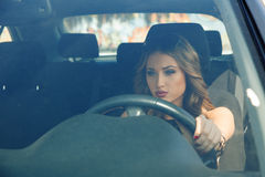 Lovely young adult girl concentrated on driving Stock Images
