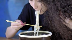 A lovely young Asian girl is eating pho soup in an Asian cafe. Takes noodles with Chinese chopsticks. Chinese. Vietnamese or Japanese cafe or restaurant stock video footage
