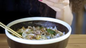 A lovely young Asian girl takes a photo of pho soup in an Asian cafe. Chinese, Vietnamese or Japanese cafe or restaurant.  stock footage