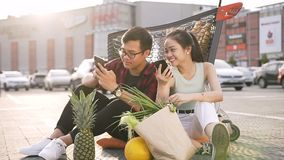 Lovely young asian man and woman in casual clothes sitting on the ground in front of supermarket and watching on their stock video footage