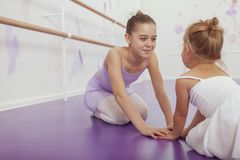 Charming two young ballerinas practicing at ballet class stock images