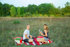 Lovely young beautiful couple resting in park. Beautiful young happy loving couple on picnic lying down on plaid  in field on sunny summer day enjoying, holding Stock Photos