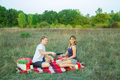 Lovely young beautiful couple resting in park. Beautiful young happy loving couple on picnic lying down on plaid  in field on sunny summer day enjoying, holding Royalty Free Stock Images