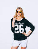 Lovely young blond woman making a call me gesture in suglasses, Sweatshirt and white shorts. White background. Indoor. Warm color. Royalty Free Stock Photo