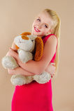 Lovely young blonde girl in a crimson dress Stock Images
