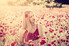Lovely young blonde girl in a poppy field at sunset. Light, vintage image. Happiness and beauty people concept stock images