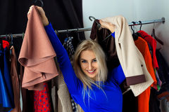 Lovely young blonde girl smiling in clothing store. Happy young lady with a lot of clothes. Shopping concept Royalty Free Stock Photos