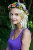 Lovely Young Blonde Lady with Garland of Flowers. Pretty blond woman with a wreath of pretty spring flowers on her head Royalty Free Stock Images