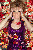Lovely young blonde lying in rose petals Stock Images