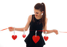 Lovely young brunette girl posing with red heart isolated on white background. Saint Valentines Day concept. Love stock photography