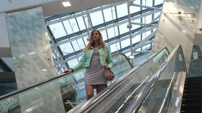 Pretty Young Brunette Woman Coming Down The Escalator. Lovely young brunette woman in a dress with a handbag and a jacket goes down the escalator. She stock video