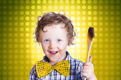 Child holding chocolate covered cooking spoon Royalty Free Stock Photos