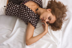 Lovely young coquette. Lying on a white silk fabric Royalty Free Stock Photo