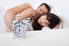 Lovely young couple and alarm clock Royalty Free Stock Photo