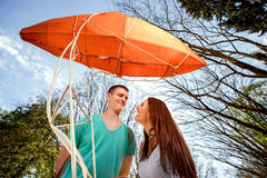 Lovely young couple flirting near the red dirigible in the park Stock Photos