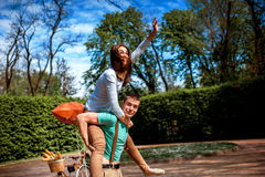 Lovely young couple having fun near the bicycle with red dirigib Royalty Free Stock Photography