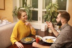 Lovely young couple having pasta carbonara for dinner stock photos