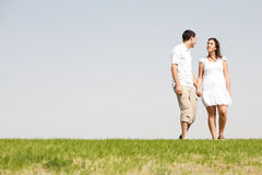Lovely young couple holding hands and walking Stock Photos