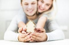 Lovely young couple holding a house layout on their outstretched hands. The concept of buying a new apartment. stock photo