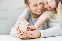Lovely young couple holding a house layout on their outstretched hands. The concept of buying a new apartment. stock photography