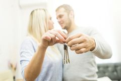 A lovely young couple holds in front of them the keys to their new apartment. royalty free stock images