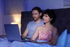 Lovely young couple with laptop on bed. At night time Royalty Free Stock Images
