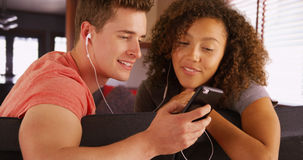 Lovely young couple listening to music on mobile device. Royalty Free Stock Photo