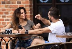 Lovely young couple looking at smart phone at cafe. Portrait of a couple sitting down at a cafe and making selfie royalty free stock photos