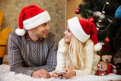 Lovely young couple in Santa`s hat looking at each other while l Royalty Free Stock Photo