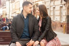 Lovely young couple sitting at the street stock images