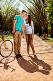 Lovely young couple standing and hugging near the bicycle in the Royalty Free Stock Photography