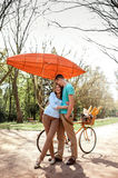Lovely young couple standing and hugging near the bicycle with r Stock Photo