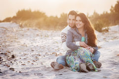 Lovely young couple on the sunset beach. Selective focus and toned image Royalty Free Stock Images