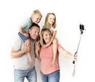 Lovely young couple taking selfie photo self portrait with stick and mobile phone carrying son and daughter on shoulders posing ha. Ppy smiling isolated on white Stock Image