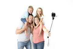 Lovely young couple taking selfie photo self portrait with stick and mobile phone carrying son and daughter on shoulders posing ha royalty free stock image