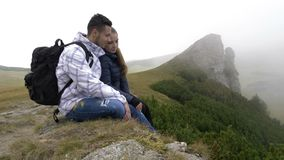 Lovely young couple of tourists resting on top of mountain kissing and enjoying the beautiful nature - stock video footage