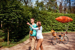 Lovely young couple walking in the park with the bicycle with re Royalty Free Stock Photography