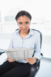 Lovely young dark haired businesswoman reading a newspaper Stock Photography