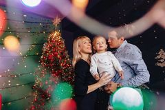 Lovely family with little baby on the background of a Christmas tree, celebrating the new year stock photos