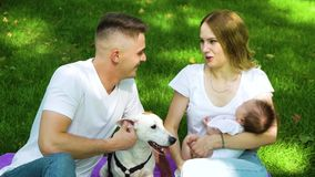 Caring family with baby and dog spending leisure time in summer park. Lovely young family with newborn baby and pet Jack Russell Terrier spending leisure time in stock footage