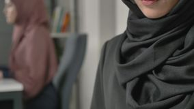 Lovely young girl in black hijab typing text on smartphone. 60 fps. 4k stock video footage