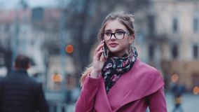 Lovely young girl calling somebody on the phone, then happily talking and smiling gladly. Stylish look, pink cozy coat stock video