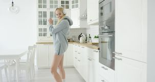 Lovely young girl dancing in kitchen stock video footage