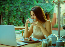 Lovely young girl drink tea and dreaming outdoors. In restaurant Stock Photography