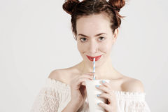 Lovely young girl is drinking with a straw with innocent smile on her face Stock Images