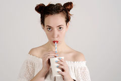 Lovely young girl is drinking with a straw with a serious face. Royalty Free Stock Photography